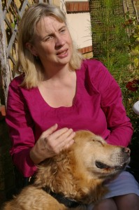 Lynn sitting looking out at camera head turned slightly to her left with Guide dog Patsy at her side