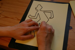 Making a drawing of a running man with wool using navy yarn on yellow paper