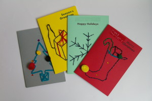 display of 4 brightly coloured Christmas cards: Christmas tree, presents, snowflake and stocking with presents