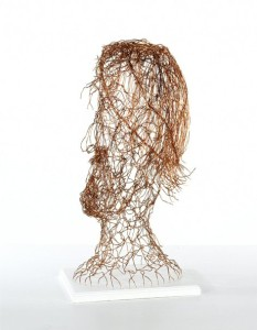 wire head sculpture on white wooden plinth
