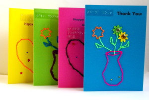 Four card display of portrait style tactile scented Brailled greetings cards in multiple bright colours