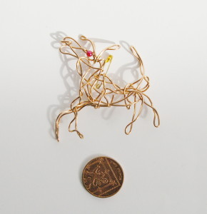 wire running dog badge placed next to 2 pence coin