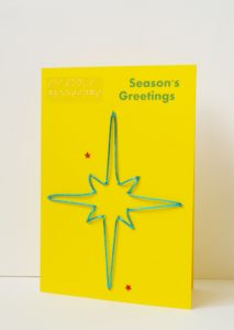 Blue sparkly star season's greetings card on yellow card