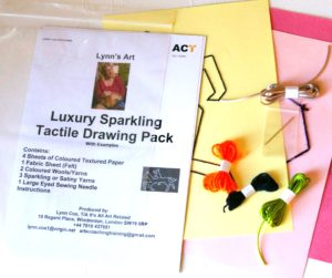 displays contents of luxury drawing pack: wools sparkly yarns, examples templates coloured textured paper